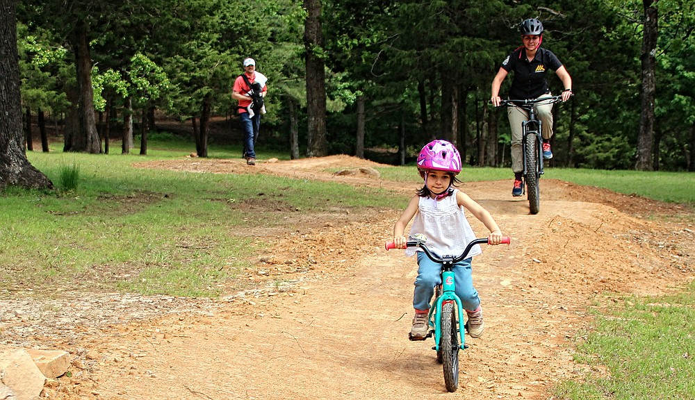 Suzanne Grobmeyer, executive director for the Arkansas Parks and Recreation Foundation, pursues her daughter Margaret with husband Andrew and son George following on a child-friendly path at Mount Nebo State Park.  (Special to the Democrat-Gazette/Bob Robinson)