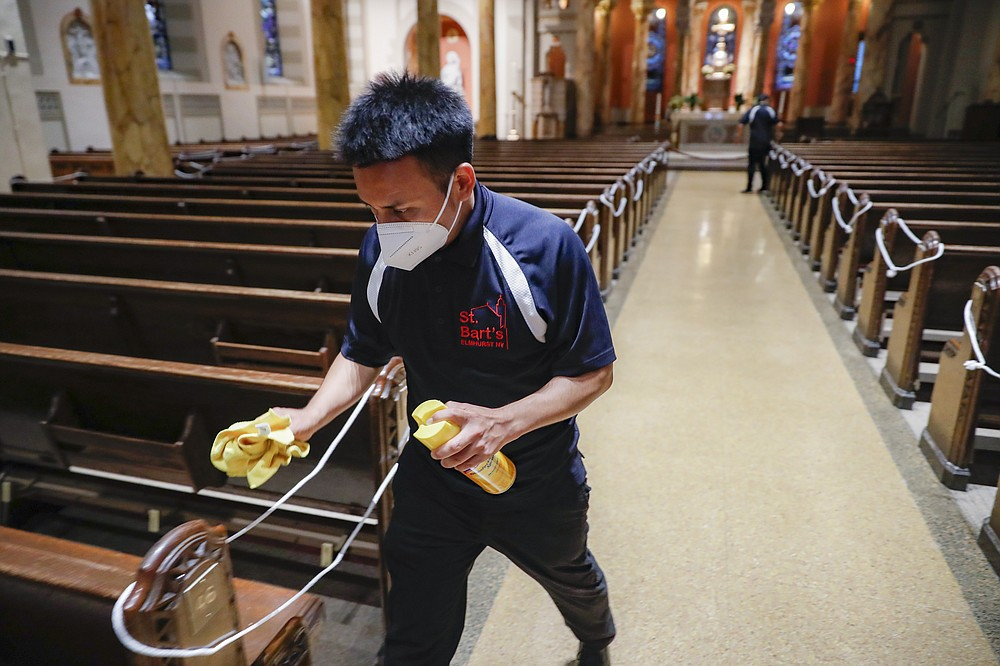 Pews are sanitized after Spanish-language Mass at St. Bartholomew Roman Catholic Church, Monday, July 6, 2020, in the Queens borough of New York. (AP Photo/John Minchillo)
