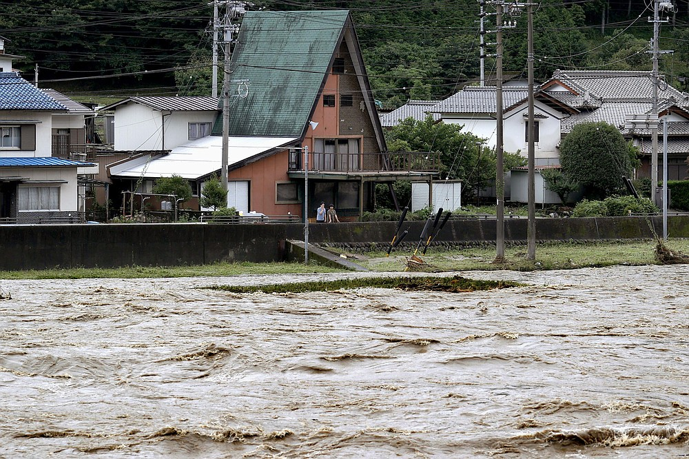 People look at swollen Hida river following heavy rain in Gero, Gifu prefecture, central Japan Wednesday, July 8, 2020. Floodwaters flowed down streets in southern Japanese towns hit by heavy rains. (Yuya Shino/Kyodo News via AP)