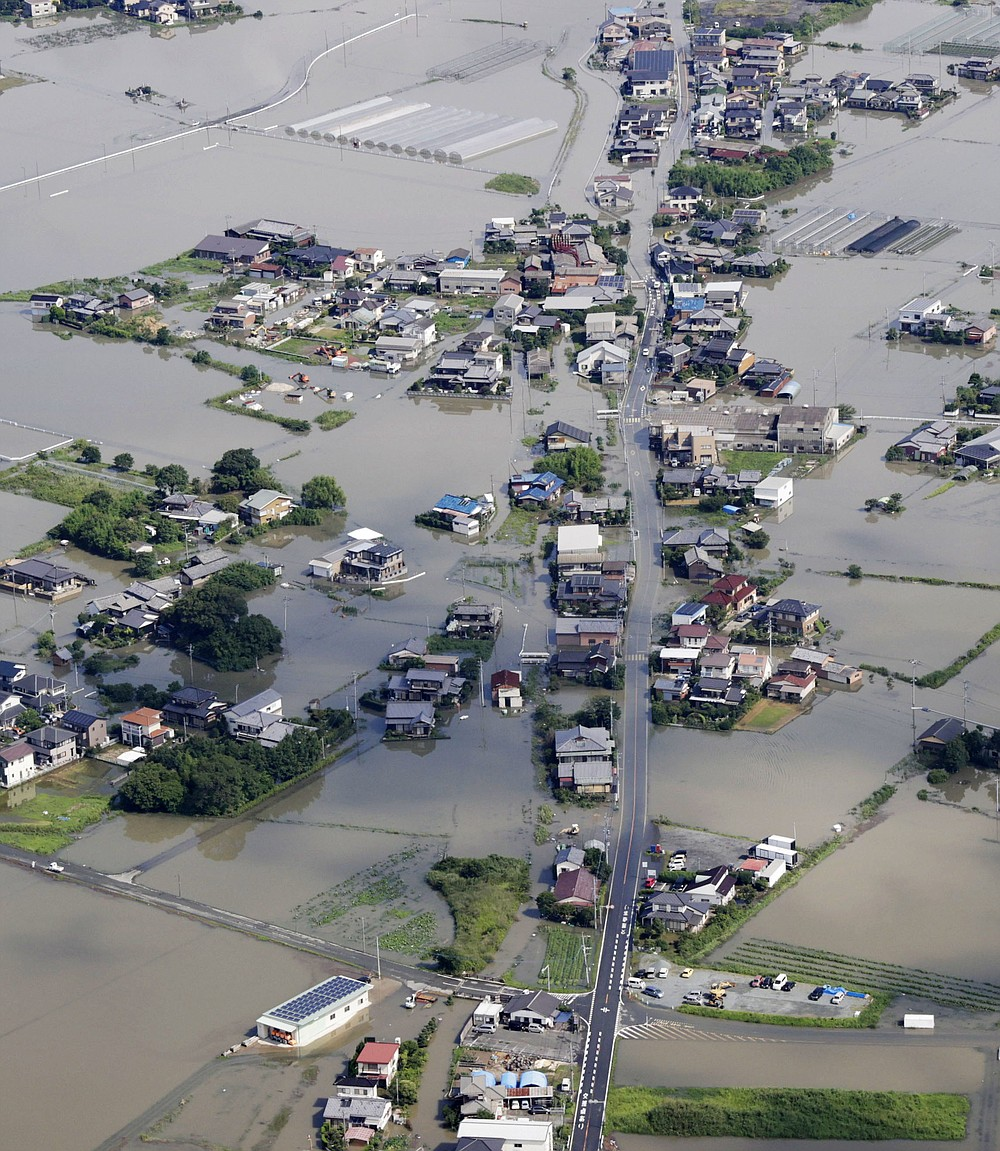 This aerial photo shows the flooded area near the swollen Chikugo River, not seen in photo, in Kurume city, Fukuoka prefecture, southern Japan Wednesday, July 8, 2020. Pounding rain that already caused deadly floods in southern Japan was moving northeast Wednesday, battering large areas of Japan's main island, swelling more rivers, triggering mudslides and destroying houses and roads. (Kyodo News via AP)