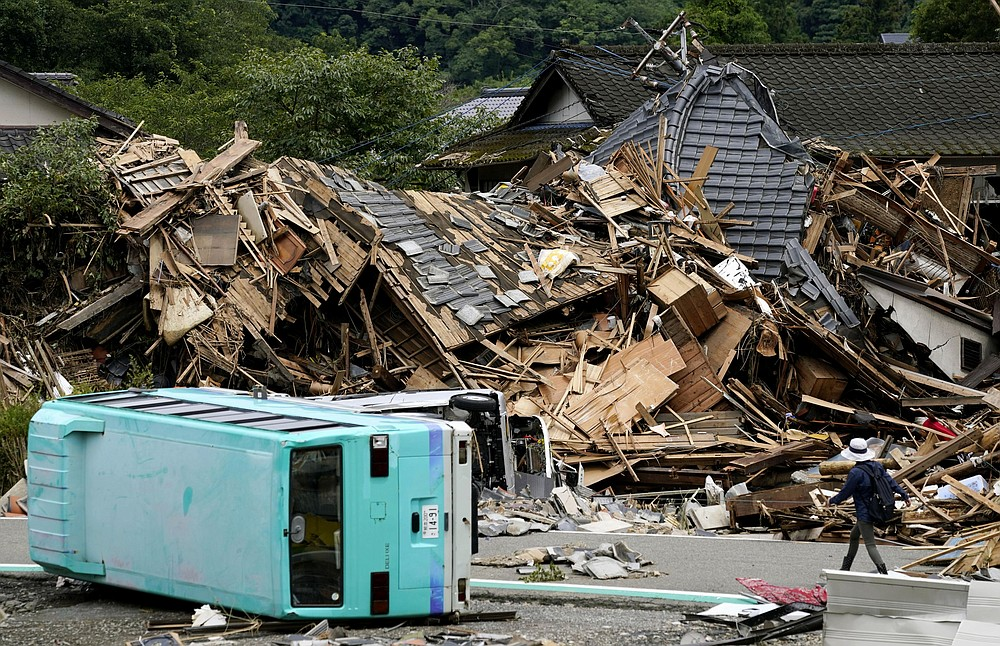 People walks past an overturned cars and the houses damaged by a flooded river in Kuma village, Kumamoto prefecture, southern Japan Wednesday, July 8, 2020. Floodwaters flowed down streets in southern Japanese towns hit by heavy rains. (Koji Harada/Kyodo News via AP)