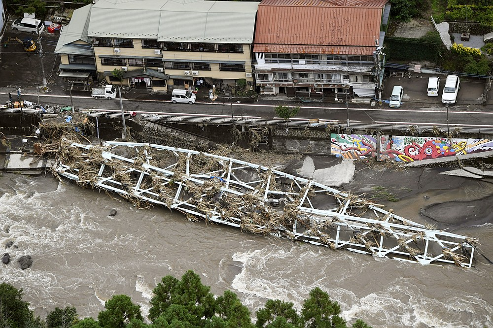 This aerial photo show a damaged bridge lies on the swollen Kusu River after heavy rains in Hita, Oita prefecture, southern Japan Wednesday, July 8, 2020. Pounding rain that already caused deadly floods in southern Japan was moving northeast Wednesday, battering large areas of Japan's main island, swelling more rivers, triggering mudslides and destroying houses and roads. (Junko Ozaki/Kyodo News via AP)