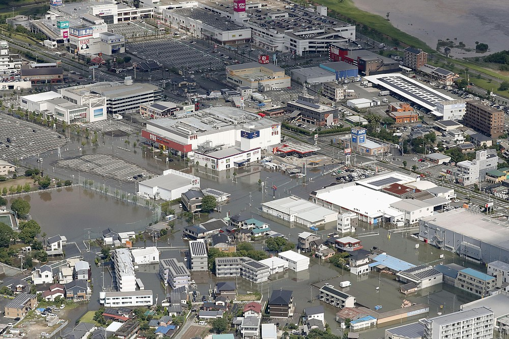 Streets are flooded following a heavy rain in Kurume, Fukuoka prefecture, southern Japan Wednesday, July 8, 2020. Floodwaters flowed down streets in southern Japanese towns hit by heavy rains. (Kyodo News via AP)