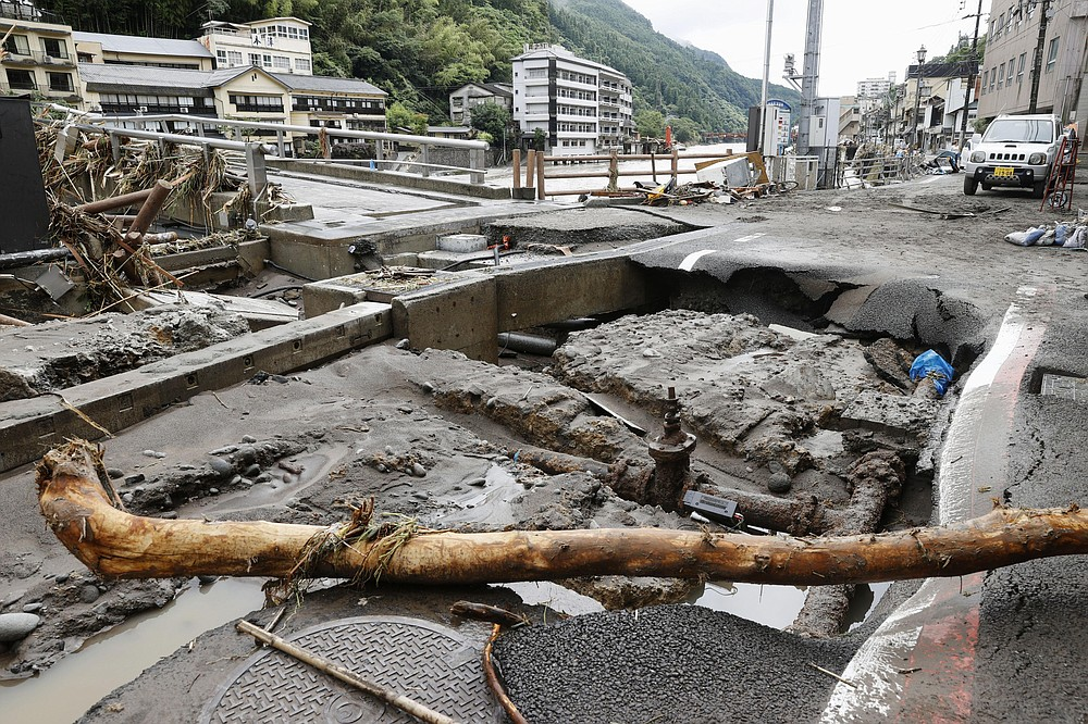 A damaged road is seen following heavy rain in Hita, Oita prefecture, southern Japan Wednesday, July 8, 2020. Floodwaters flowed down streets in southern Japanese towns hit by heavy rains. (Miyuki Saito/Kyodo News via AP)