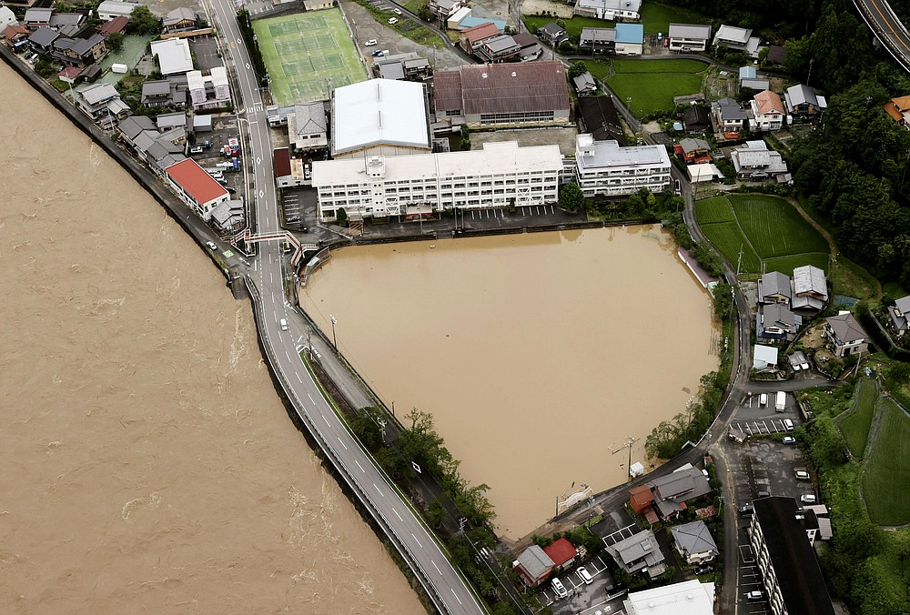 A schoolyard of a junior high school is seen flooded following heavy rains in Gero, Gifu prefecture, central Japan Wednesday, July 8, 2020. Floodwaters flowed down streets in southern Japanese towns hit by heavy rains. (Kyodo News via AP)