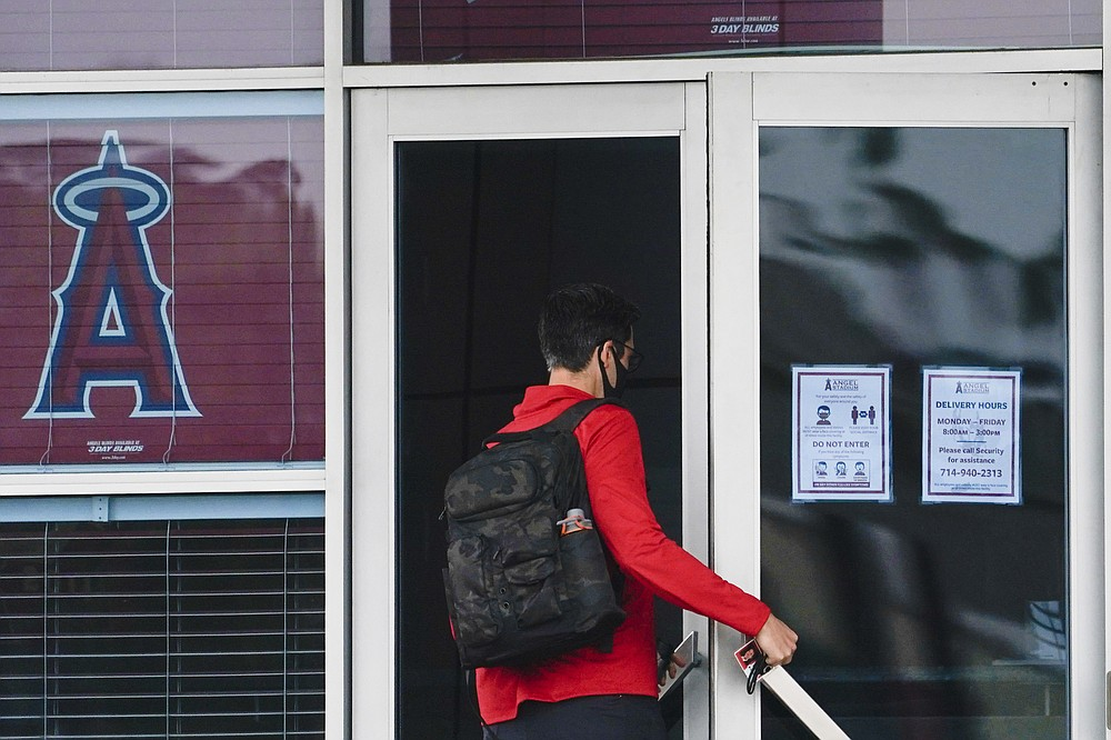 A Los Angeles Angels employee enters Angels Stadium on Wednesday, July 1, 2020, in Anaheim, Calif. The Angels and other Major League Baseball teams will report to their respective facilities for training this week, amid the coronavirus pandemic. (AP Photo/Ashley Landis)