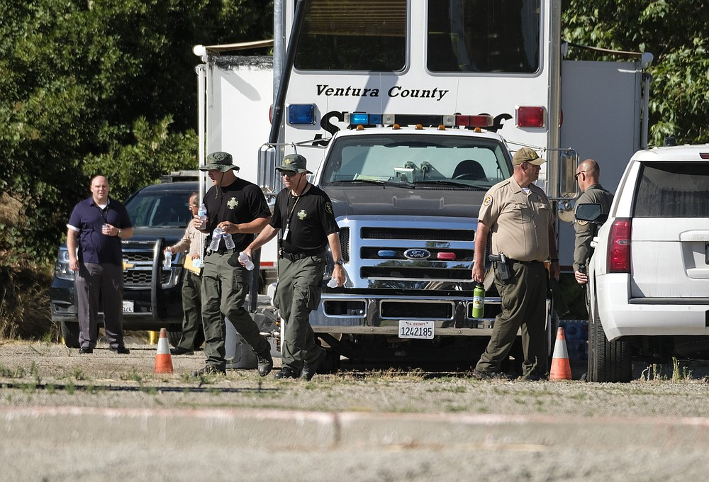 """Ventura County Sheriff's deputies appear on the scene in Lake Peru, Calif., Thursday, July 9, 2020, searching for """"Glee"""" star Naya Rivera who was reported missing on Wednesday. Her 4-year-old son was found alone on a rented boat. (AP Photo/Ringo H.W. Chiu)"""