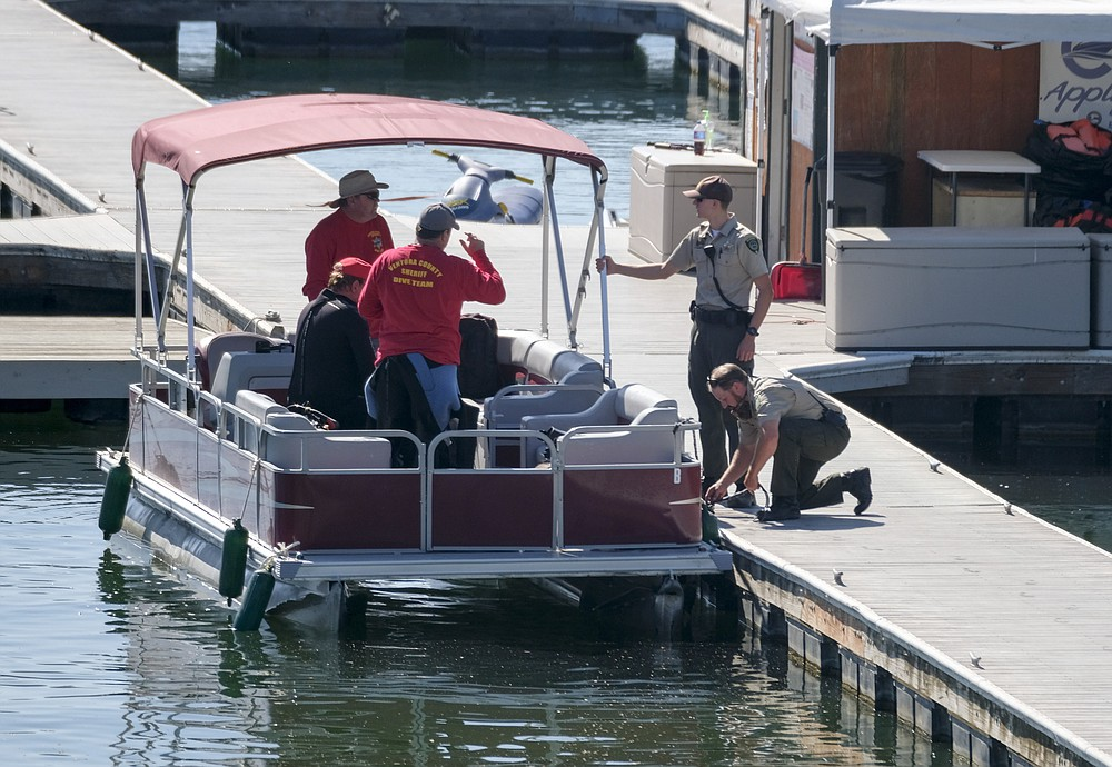 """Members of Ventura County Sheriff's Office Underwater Search and Rescue Team help in the search for former """"Glee"""" star Naya Rivera, Thursday, July 9, 2020 in Lake Peru, Calif.  (AP Photo/Ringo H.W. Chiu)"""