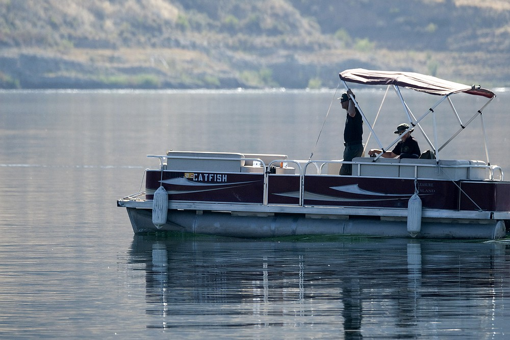 """Members of Ventura County Sheriff's Office Underwater Search and Rescue Team search for former """"Glee"""" actress Naya Rivera, Thursday, July 9, 2020 in Lake Peru, Calif. Rivera rented a boat on Wednesday and her 4-year-old son was found alone on the rented boat. (AP Photo/Ringo H.W. Chiu)"""
