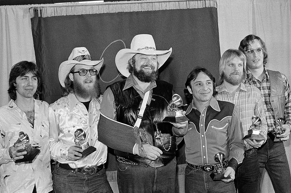 """FILE - Charlie Daniels, center, joins members of the Charlie Daniels Band with their Grammy Awards in Los Angeles on Feb. 27, 1980, as best country vocal performance by a group for their hit """"The Devil Went Down To Georgia."""" Daniels has died at age 83. A statement from his publicist said the Country Music Hall of Famer died Monday, July 6, 2020, due to a hemorrhagic stroke.  (AP Photo/Lennox McLendon, File)"""