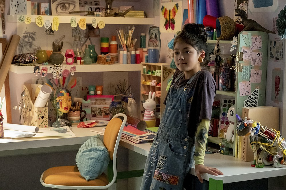 "This image released by Netflix shows Momona Tamada portraying Claudia Kishi in a scene from the Netflix series ""The Baby-Sitters Club,"" based on the popular book series. With 180 million copies in print worldwide, ""The Baby-Sitters Club"" books were a juggernaut during their 1986-2000 run. They follow Claudia, Kristy, Mary Anne, Stacey and Dawn and their babysitting adventures in the fictional suburb of Stoneybrook, Connecticut.  (Kailey Schwerman/Netflix via AP)"
