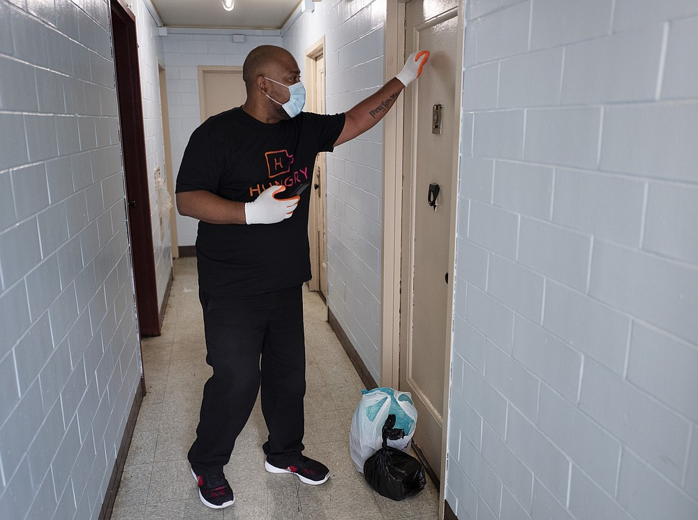Driver Frank Robinson knocks on an apartment door as he delivers prepackaged meals for breakfast, lunch and dinner in Brooklyn, Tuesday, July 7, 2020, in New York. The city provides HUNGRY with a list of names of those who have requested food subsidies. (AP Photo/Mark Lennihan)