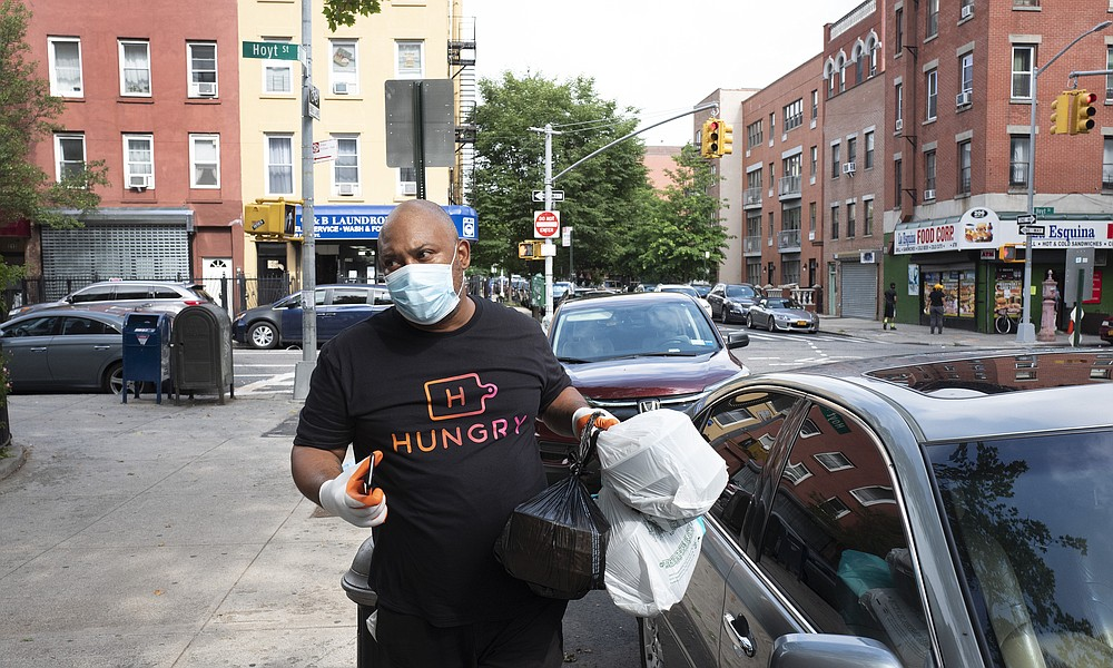Driver Frank Robinson delivers prepackaged meals in New York on Tuesday, July 7, 2020. Catering startup HUNGRY pays more than 200 drivers to deliver prepackaged meals to stay-at-home elderly and low-income kids. (AP Photo/Mark Lennihan)