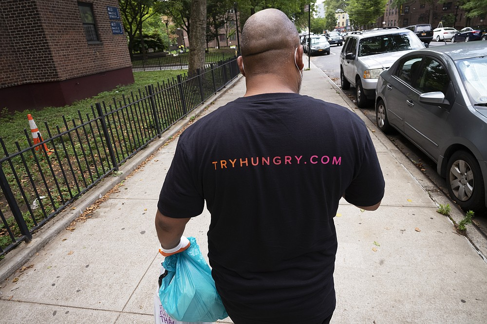 Driver Frank Robinson delivers prepackaged meals Tuesday, July 7, 2020 in New York. Robinson is one of 200 drivers paid by catering startup HUNGRY to deliver prepackaged meals to stay-at-home elderly and low-income kids. (AP Photo/Mark Lennihan)