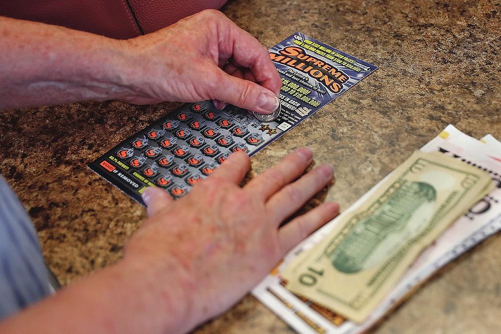 Seorang wanita menggaruk tiket instan $ 30 sambil bermain lotere di Ted's Stateline Mobil pada hari Rabu, 24 Juni 2020 di Methuen, Mass. Pandemi virus corona telah menjadi rollercoaster untuk lotere negara di seluruh negeri, dengan beberapa mendapat dorongan dari penurunan ekonomi dan lainnya berjuang untuk menebus kekurangan pendapatan. (Foto AP / Charles Krupa)