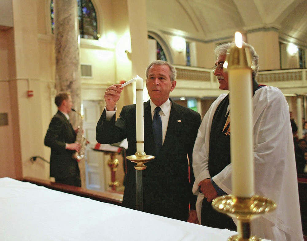 """FILE - In this Tuesday, Sept. 11, 2007 photo provided by the White House, President George W. Bush lights a candle accompanied by Rev. Luis Leon, during a service of prayer and remembrance at St. John's Episcopal Church in Washington marking the sixth anniversary of the Sept. 11 terrorist attacks. """"If he was in town, he was in church,"""" Leon said of the younger Bush. (Eric Draper/White House via AP)"""