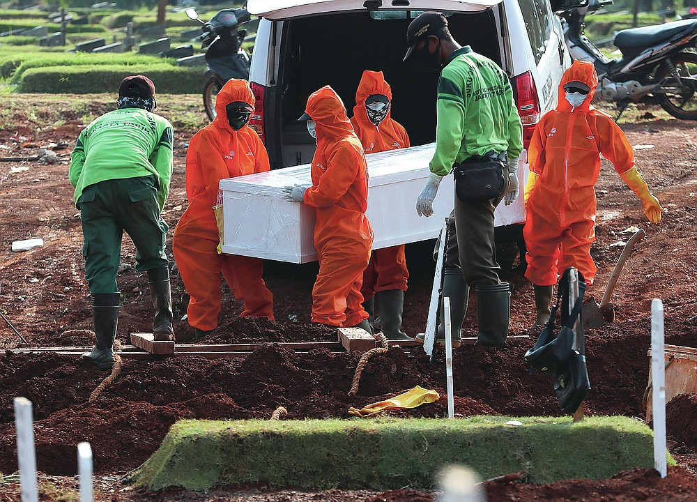 Workers in protective suits carry a coffin containing the body of someone who presumably died of COVID-19 during a burial at a special cemetery for the new coronavirus victims in Jakarta, Indonesia Friday, June 12, 2020. As Indonesia's virus death toll rises, the world's most populous Muslim country finds itself at odds with protocols put in place by the government to handle the bodies of victims of the pandemic. This has led to increasing incidents of bodies being taken from hospitals, rejection of COVID-19 health and safety procedures, and what some experts say is a lack of communication from the government. (AP Photo/Achmad Ibrahim)