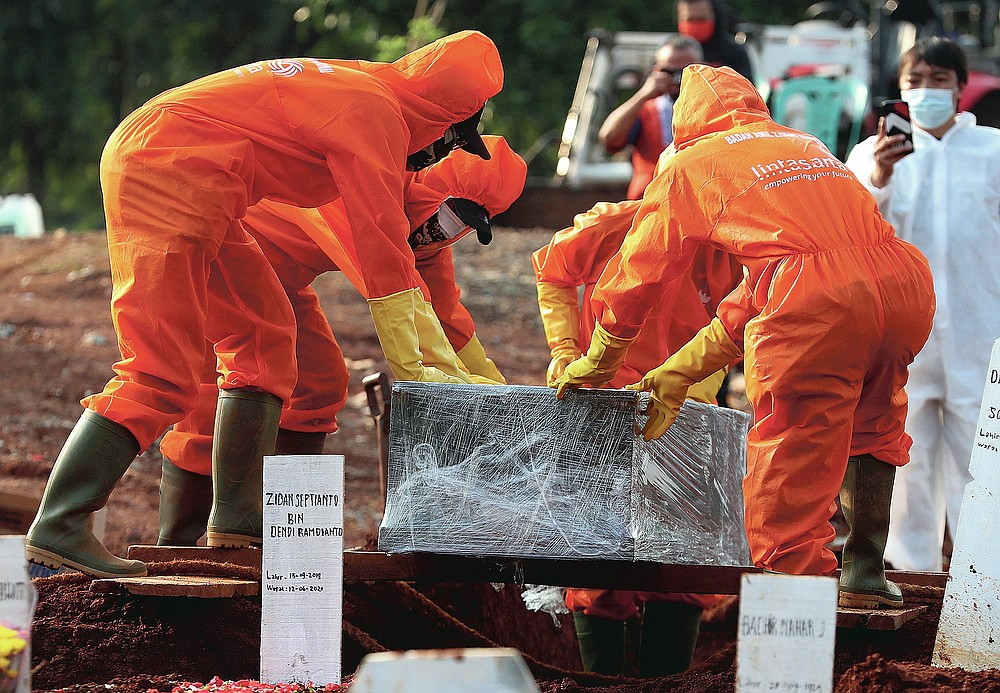 Workers in protective suits prepare a coffin containing the body of someone who presumably died of COVID-19 for burial at a cemetery in Jakarta, Indonesia Friday, June 12, 2020. As Indonesia's virus death toll rises, the world's most populous Muslim country finds itself at odds with protocols put in place by the government to handle the bodies of victims of the pandemic. This has led to increasing incidents of bodies being taken from hospitals, rejection of COVID-19 health and safety procedures, and what some experts say is a lack of communication from the government. (AP Photo/Achmad Ibrahim)