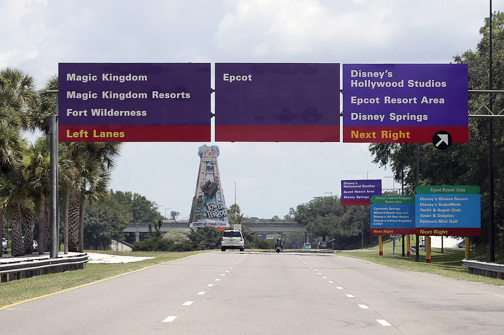Signs direct motorists to the various theme parks at Walt Disney World, Thursday, July 2, 2020, in Lake Buena Vista, Fla. Magic Kingdom and Animal Kingdom will reopen on July 11. Disney World's other two parks, Epcot and Disney's Hollywood Studios, will welcome back guests four days later. (AP Photo/John Raoux)