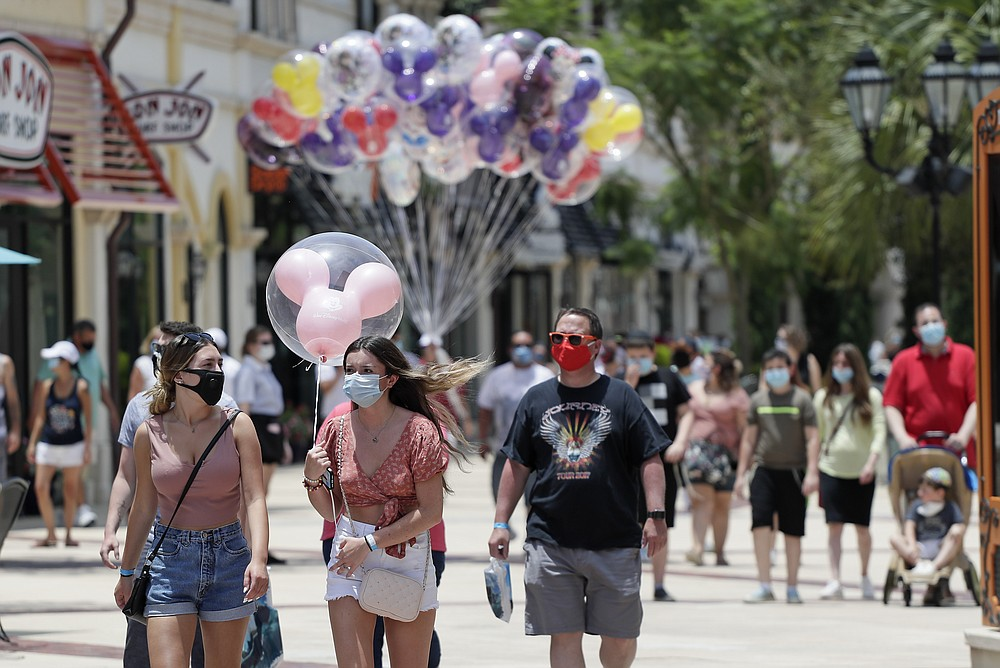 FILE - In this June 16, 2020, file photo, guests required to wear masks because of the coronavirus stroll through the Disney Springs shopping, dining and entertainment complex in Lake Buena Vista, Fla. Magic Kingdom and Animal Kingdom will reopen on July 11. In May, the company opened Disney Springs. (AP Photo/John Raoux, File)
