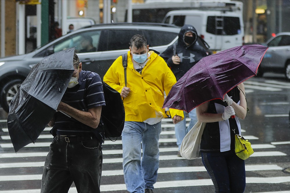 Pedestrians use umbrellas to protect themselves from inclement weather brought about by Tropical Storm Fay, Friday, July 10, 2020, in New York. Beaches closed in Delaware and rain lashed the New Jersey shore as fast-moving Tropical Storm Fay churned north on a path expected to soak the New York City region. (AP Photo/Frank Franklin II)