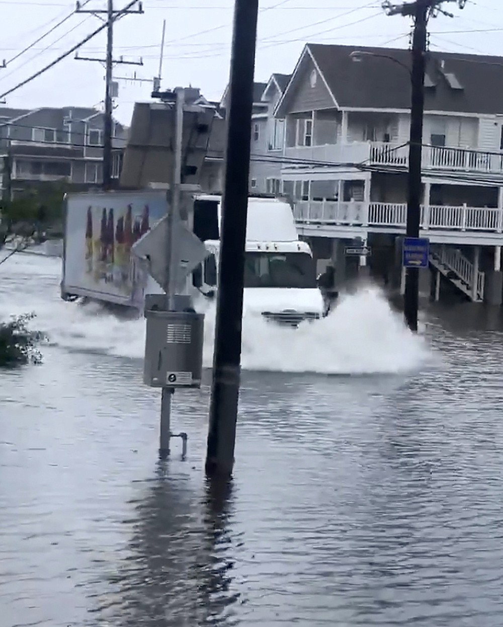 A tractor-trailer plows through standing water on a flooded Sea Isle City street, on New Jersey's Long Beach Island, Friday, July 10, 2020, in this photo made from video provided by Anthony Kutschera Jr. The Jersey shore was lashed Friday as the fast-moving Tropical Storm Fay churned north on a path expected to soak the New York City region. (Anthony Kutschera Jr. via AP)