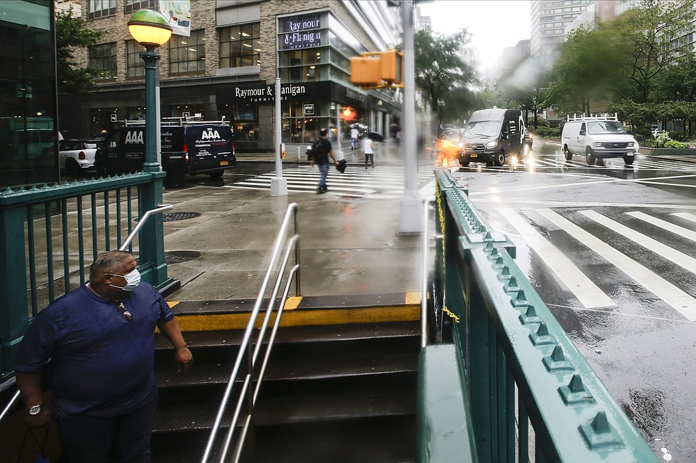 A man observes the street as he enters the Lincoln Center subway station during a heavy rain shower brought about by Tropical Storm Fay Friday, July 10, 2020, in New York. Beaches closed in Delaware and rain lashed the New Jersey shore as fast-moving Tropical Storm Fay churned north on a path expected to soak the New York City region. (AP Photo/Frank Franklin II)