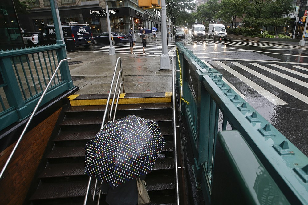 A woman uses an umbrella as she exits the Lincoln Center subway station during a rain shower brought about by Tropical Storm Fay, Friday, July 10, 2020, in New York. Beaches closed in Delaware and rain lashed the New Jersey shore as fast-moving Tropical Storm Fay churned north on a path expected to soak the New York City region. (AP Photo/Frank Franklin II)