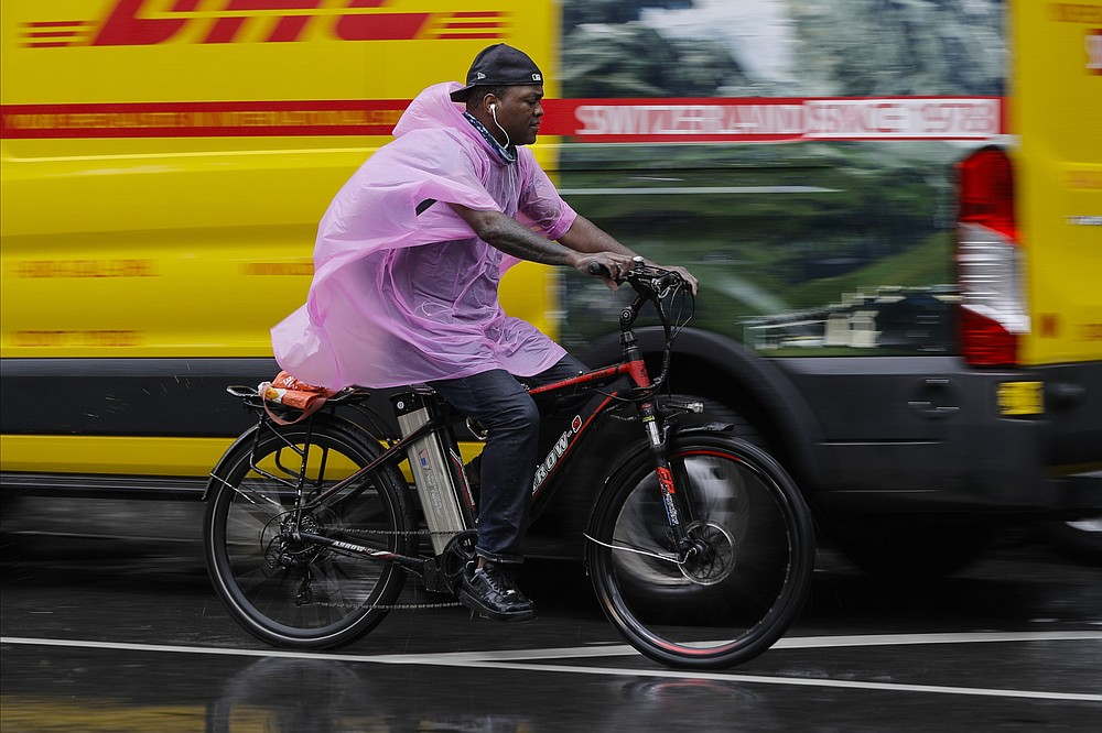 A cyclist uses a plastic rain cover to protect themselves from rain brought about by Tropical Storm Fay Friday, July 10, 2020, in New York. Beaches closed in Delaware and rain lashed the New Jersey shore as fast-moving Tropical Storm Fay churned north on a path expected to soak the New York City region. (AP Photo/Frank Franklin II)