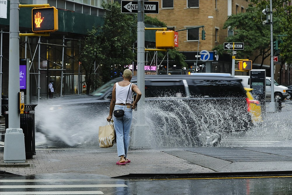 A pedestrian avoids being splashed by passing automobiles during heavy rain brought by Tropical Storm Fay, Friday, July 10, 2020, in New York. Beaches closed in Delaware and rain lashed the New Jersey shore as fast-moving Tropical Storm Fay churned north on a path expected to soak the New York City region. (AP Photo/Frank Franklin II)