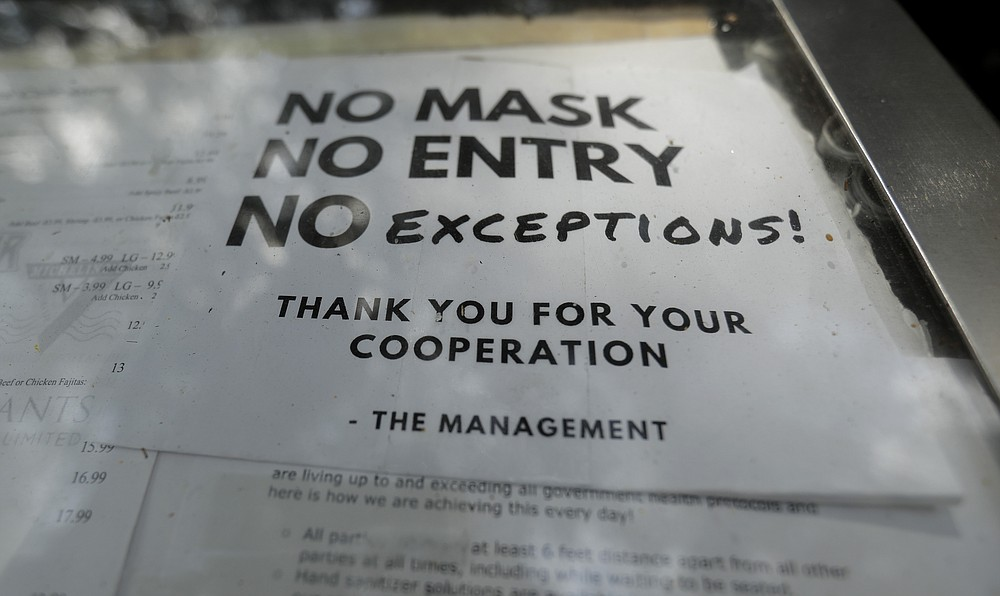 A sign requiring face masks to protect against the spread of COVID-19 is seen at a restaurant, Tuesday, July 7, 2020, in San Antonio. Texas Gov. Greg Abbott has declared masks or face coverings must be worn in public across most of the state as local officials across the state say their hospitals are becoming increasingly stretched and are in danger of becoming overrun as cases of the coronavirus surge. (AP Photo/Eric Gay)