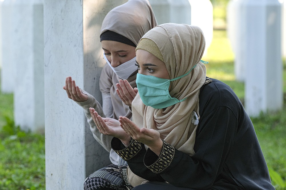Women pray in the memorial cemetery in Potocari, near Srebrenica, Bosnia, Saturday, July 11, 2020. Nine newly found and identified men and boys were laid to rest as Bosnians commemorate 25 years since more than 8,000 Bosnian Muslims perished in 10 days of slaughter, after Srebrenica was overrun by Bosnian Serb forces during the closing months of the country's 1992-95 fratricidal war, in Europe's worst post-WWII massacre. (AP Photo/Kemal Softic)