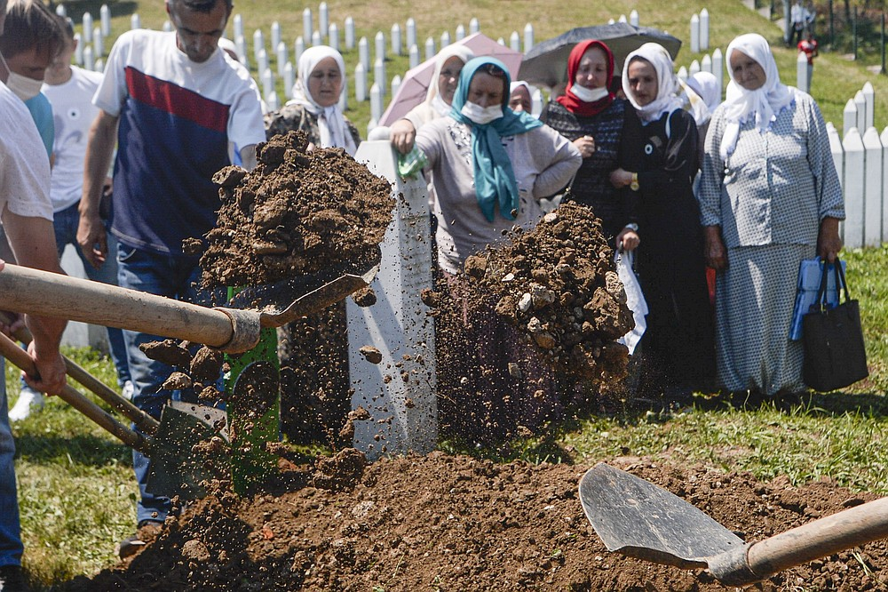 Women watch as one of the massacre victims is buried in Potocari, near Srebrenica, Bosnia, Saturday, July 11, 2020. Mourners converged on the eastern Bosnian town of Srebrenica for the 25th anniversary of the country's worst carnage during the 1992-95 war and the only crime in Europe since World War II that has been declared a genocide. (AP Photo/Kemal Softic)