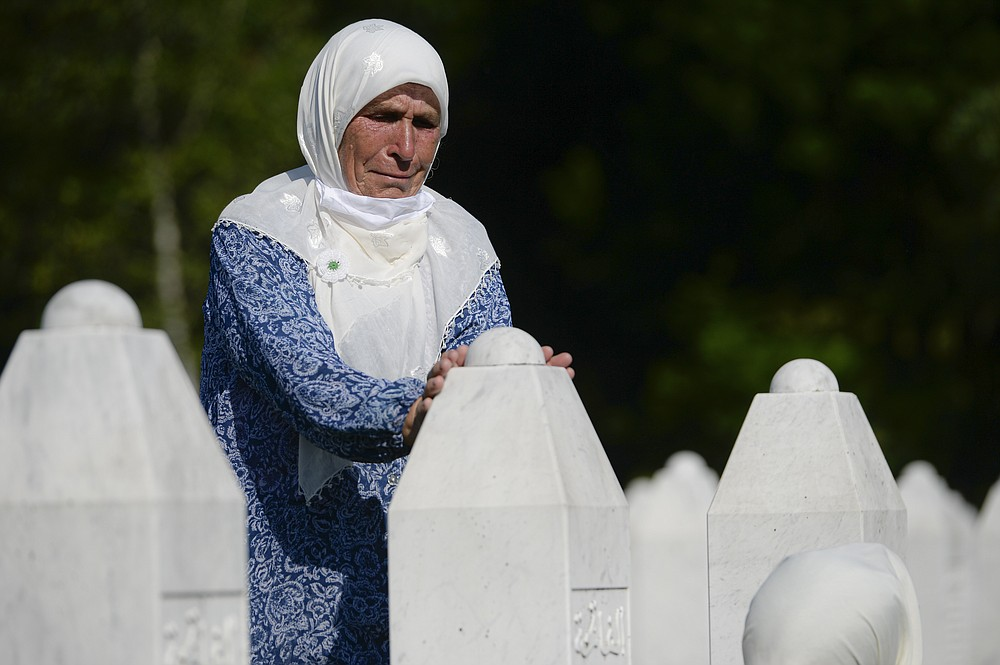 A woman touches a gravestone in Potocari, near Srebrenica, Bosnia, Saturday, July 11, 2020. Nine newly found and identified men and boys were laid to rest as Bosnians commemorate 25 years since more than 8,000 Bosnian Muslims perished in 10 days of slaughter, after Srebrenica was overrun by Bosnian Serb forces during the closing months of the country's 1992-95 fratricidal war, in Europe's worst post-WWII massacre. (AP Photo/Kemal Softic)