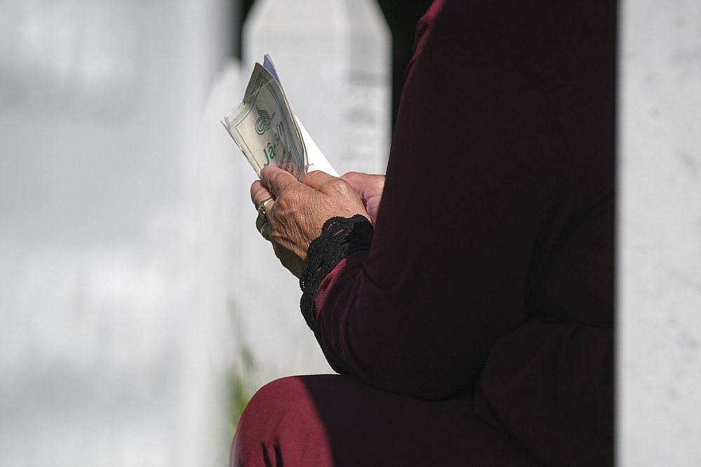 A woman prays in Potocari, near Srebrenica, Bosnia, Saturday, July 11, 2020. Nine newly found and identified men and boys were laid to rest as Bosnians commemorate 25 years since more than 8,000 Bosnian Muslims perished in 10 days of slaughter, after Srebrenica was overrun by Bosnian Serb forces during the closing months of the country's 1992-95 fratricidal war, in Europe's worst post-WWII massacre. (AP Photo/Kemal Softic)