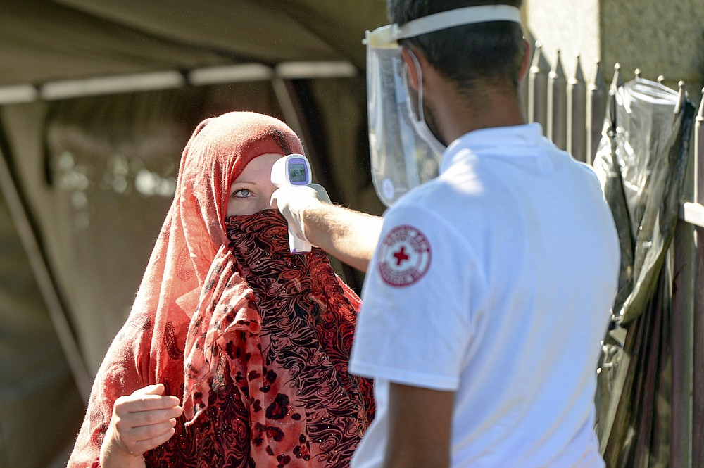 A health worker measures the temperature of a woman before granting her access to the memorial cemetery in Potocari, near Srebrenica, Bosnia, Saturday, July 11, 2020. Nine newly found and identified men and boys were laid to rest as Bosnians commemorate 25 years since more than 8,000 Bosnian Muslims perished in 10 days of slaughter, after Srebrenica was overrun by Bosnian Serb forces during the closing months of the country's 1992-95 fratricidal war, in Europe's worst post-WWII massacre. (AP Photo/Kemal Softic)