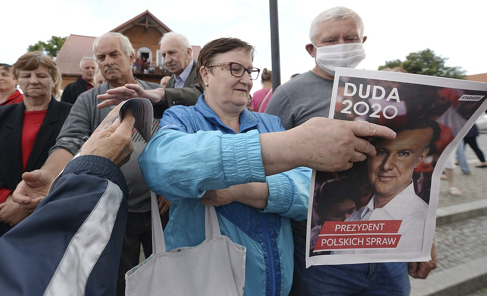 In this Tuesday, July 7, 2020 photo supporters of conservative incumbent president Andrzej Duda, who is seeking reelection in a tight presidential election runoff on Sunday, July 12, 2020 atttend a rally in Tykocin, Poland. Duda, who has backing from Poland's ruling right-wing party, is running against liberal Warsaw mayor, Rafal Trzaskowski. Opinion polls suggest the election may be decided by a small number of votes. (AP Photo/Czarek Sokolowski)