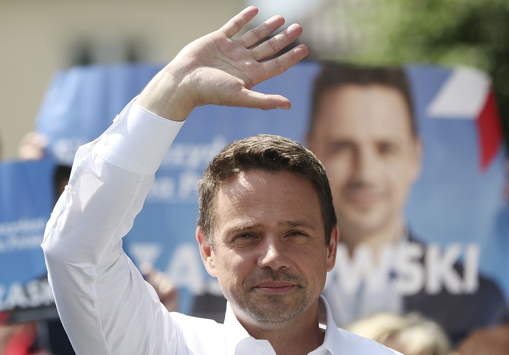 In this Thursday, July 9, 2020 photo Rafal Trzaskowski, contender in Poland's tight presidential election runoff on Sunday, July 12, 2020, waves during a rally in Raciaz, Poland. Trzaskowski is running against incumbent conservative president, Andrzej Duda, who has backing from the ruling party. Opinion polls suggest the election may be decided by a small number of votes. (AP Photo/Czarek Sokolowski)