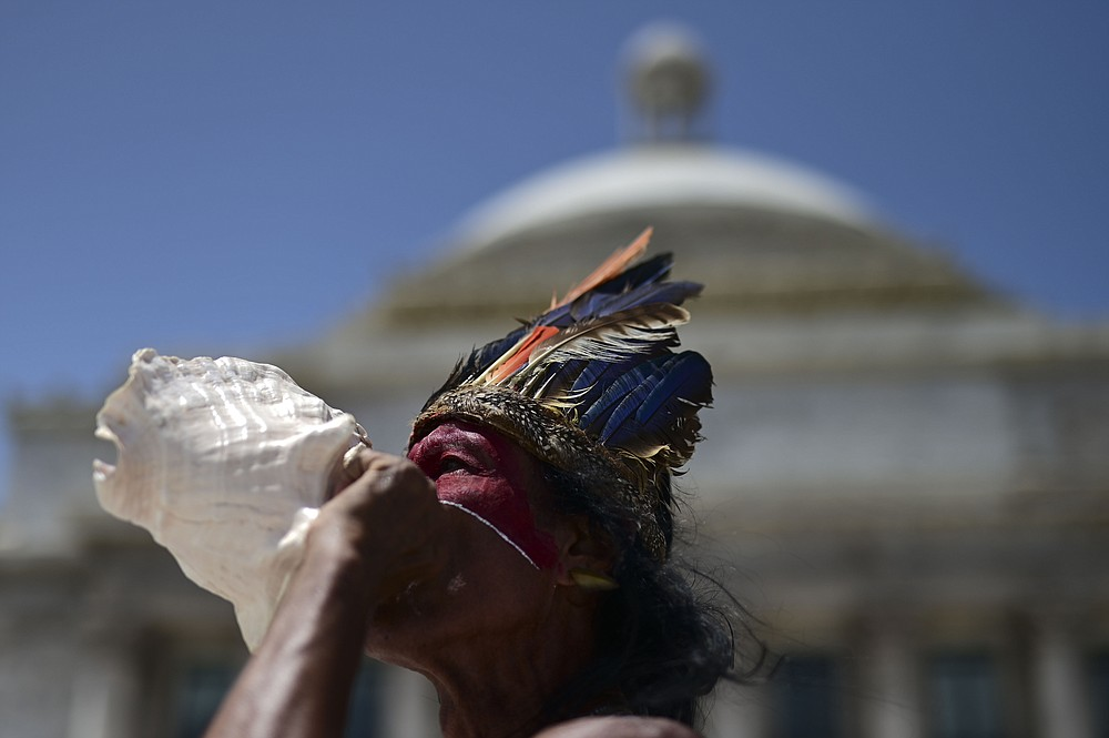 Baracutey blows on a conch shell outside the Capitol building while joining a group of activists demanding statues and street names commemorating symbols of colonial oppression be removed, in San Juan, Puerto Rico, Saturday, July 11, 2020.  Dozens of activists marched through the historic part of Puerto Rico's capital on Saturday to demand that the U.S. territory's government start by removing statues, including those of explorer Christopher Columbus.  (AP Photo/Carlos Giusti)