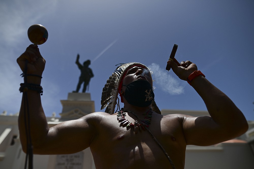Gypsy Cordova blows smoke and shakes a maraca in front of a Juan Ponce de Leon monument while leading a group of activists in a march demanding statues and street names commemorating symbols of colonial oppression be removed, in San Juan, Puerto Rico, Saturday, July 11, 2020.  Dozens of activists marched through the historic part of Puerto Rico's capital on Saturday to demand that the U.S. territory's government start by removing statues, including those of explorer Christopher Columbus.  (AP Photo/Carlos Giusti)