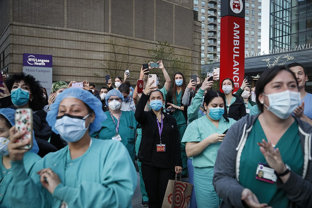 FILE - In this April 28, 2020, file photo Medical personnel attend a daily 7 p.m. applause in their honor, during the coronavirus pandemic outside NYU Langone Medical Center in the Manhattan borough of New York. Essential workers are lauded for their service and hailed as everyday heroes. But in most states nurses, first responders and frontline workers who get COVID-19 on the job have no guarantee they'll qualify for workers' comp to cover lost wages and medical care. (AP Photo/John Minchillo, File)