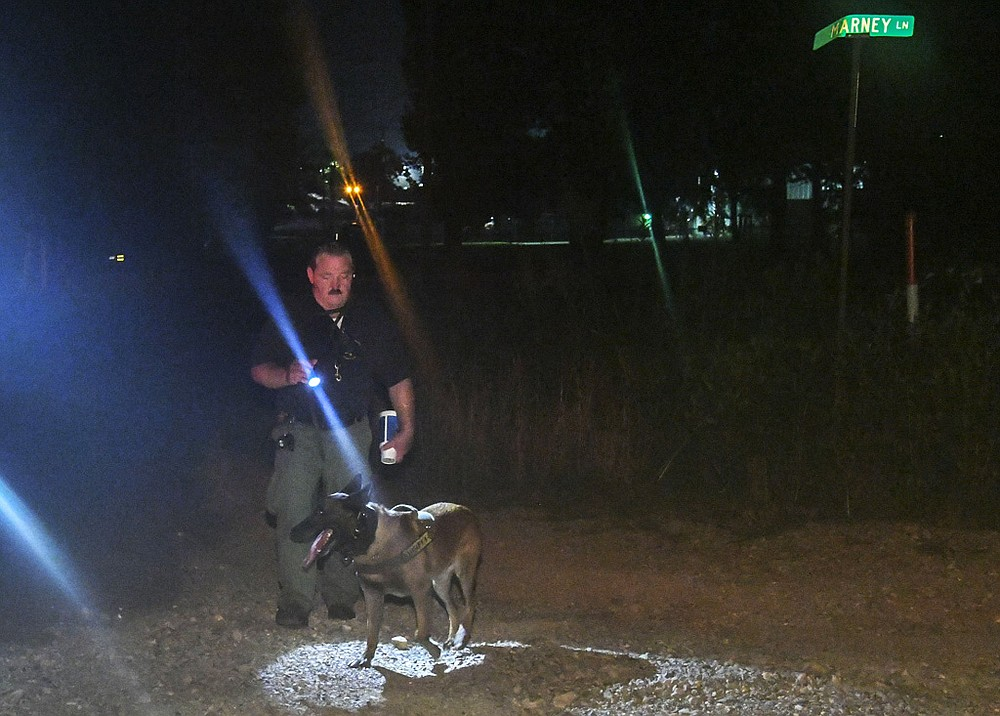 A Garland County sheriff's deputy and K-9 Officer search the scene an area of Akers Road at the Marney Lane intersection, near where a double homicide occurred at an apartment complex in the 900 block of Akers Road on Saturday. - Photo by Grace Brown of The Sentinel-Record