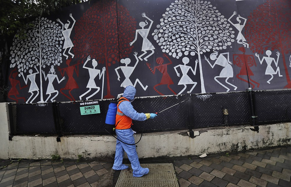 A civic worker sanitizes the gate of Bollywood superstar Amitabh Bachchan's residence after Bachchan and his son Abhishek Bachchan tested positive for the coronavirus and were hospitalized in Mumbai, India, Sunday, July 12, 2020. (AP Photo/Rafiq Maqbool)