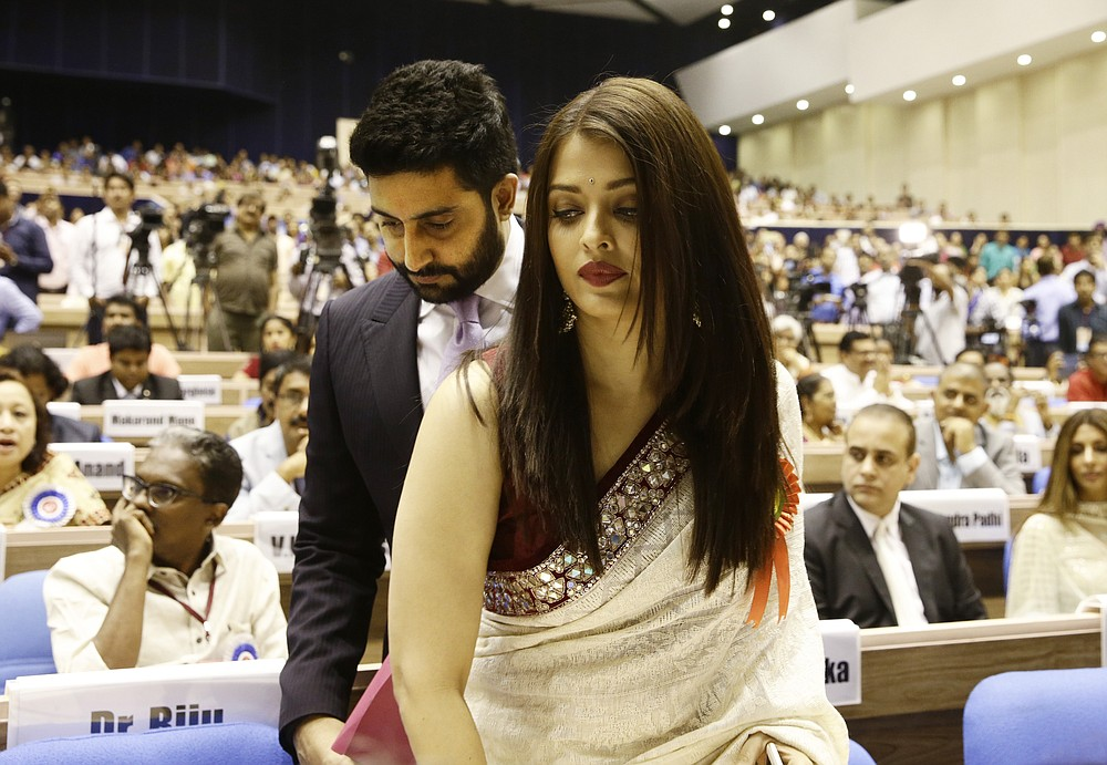 FILE- In this May 3, 2016 file photo, Bollywood couple Abhishek Bachchan, behind and Aishwarya Rai Bachchan arrive to attend the national film awards presentation ceremony in New Delhi, India. Bollywood superstar Amitabh Bachchan, his son Abhishek and two other family members including Aishwarya have tested positive for the coronavirus in Mumbai, India's financial and entertainment capital, a government minister said Sunday. (AP Photo/Saurabh Das, File)