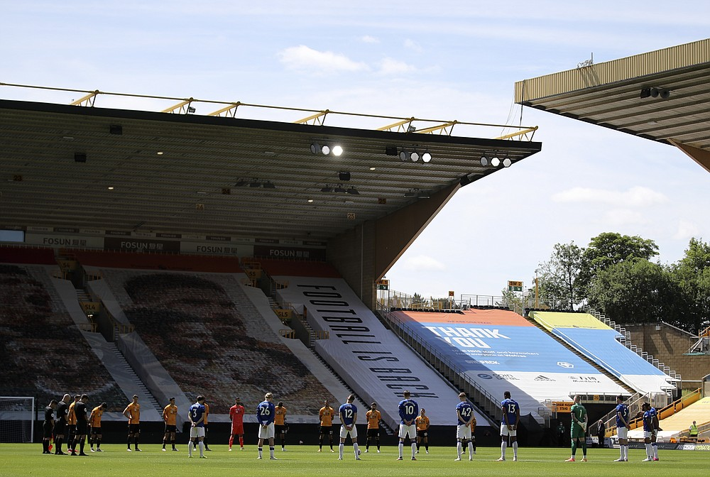 Players observe a minute of silence in memory of Jack Charlton prior to the start of the English Premier League soccer match between Watford and Everton at the Molineux Stadium in Wolverhampton, England, Sunday, July 12, 2020. (Molly Darlington/Pool via AP)