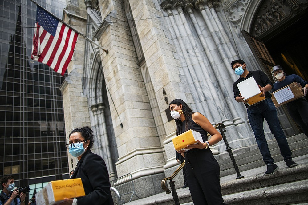 Mourners carry out the remains of loved ones following the blessing of the ashes of Mexicans who died from COVID-19 at St. Patrick's Cathedral, Saturday, July 11, 2020, in New York. The ashes were blessed before they were repatriated to Mexico. (AP Photo/Eduardo Munoz Alvarez)
