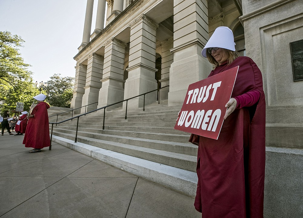 """File-Michelle Disher, from Roswell, and others dressed as characters from """"The Handmaid's Tale"""", protest outside the Capitol where Georgia's Republican Gov. Brian Kemp, was to sign the legislation, Tuesday, May 7, 2019, in Atlanta, banning abortions once a fetal heartbeat can be detected, which can be as early as six weeks before many women know they're pregnant.  A federal judge is permanently blocking Georgia's 2019 """"heartbeat"""" abortion law, finding that it violates the U.S. Constitution. U.S. District Judge Steve Jones ruled against the state Monday, July 13, 2020, in a lawsuit filed by abortion providers and an advocacy group. (Bob Andres/Atlanta Journal-Constitution via AP, File)"""