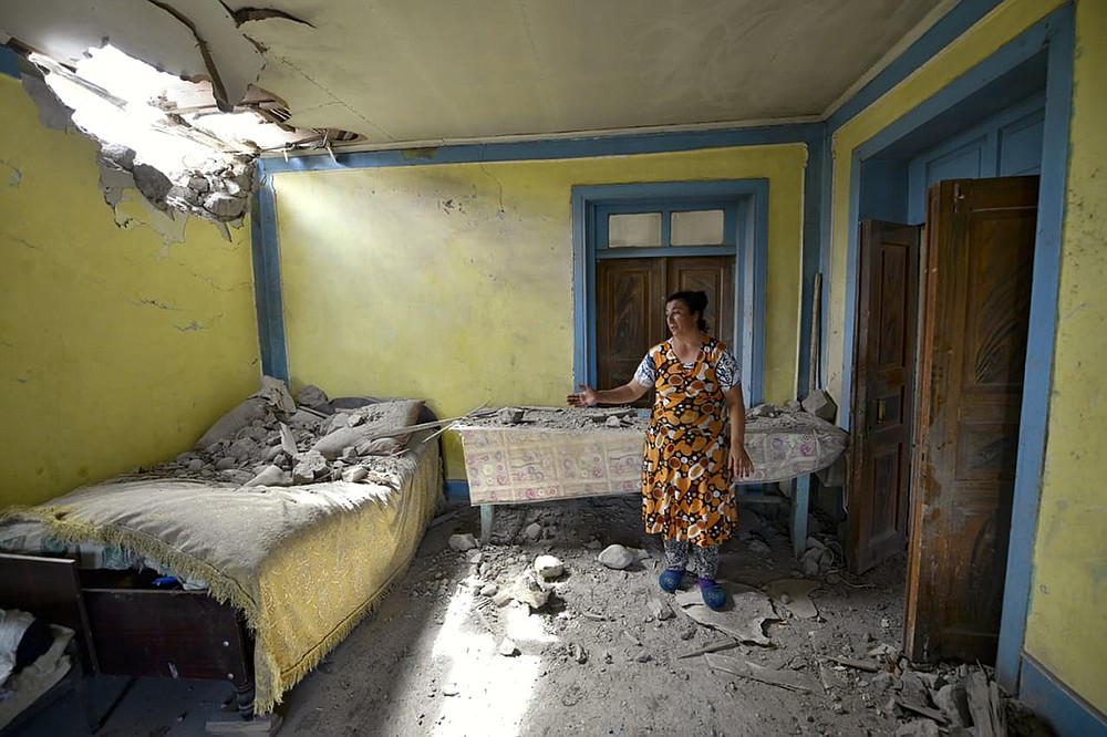 A local woman shows damage in her house after the shelling by Armenian forces in the Tovuz region of Azerbaijan, Tuesday, July 14, 2020. Skirmishes on the volatile Armenia-Azerbaijan border escalated Tuesday, marking the most serious outbreak of hostilities between the neighbors since the fighting in 2016. (AP Photo/Ramil Zeynalov)