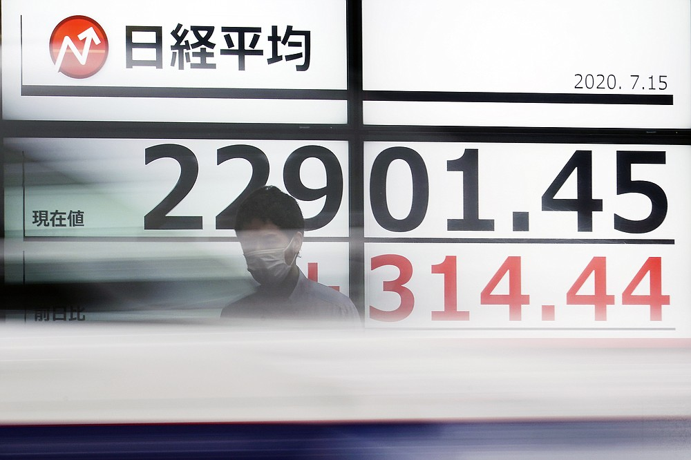 A man stands in front of an electronic stock board showing Japan's Nikkei 225 index at a securities firm as a car passes by in Tokyo Wednesday, July 15, 2020. Shares were mostly higher in Asia on Wednesday as investors were encouraged by news that an experimental COVID-19 vaccine under development by Moderna and the U.S. National Institutes of Health revved up people's immune systems just as desired. (AP Photo/Eugene Hoshiko)