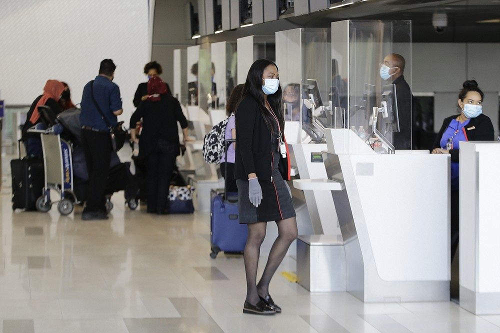 Ticket agents wear protective masks during the coronavirus pandemic while helping travelers at LaGuardia Airport, Wednesday, July 15, 2020, in New York. (AP Photo/Frank Franklin II)
